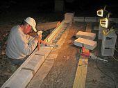 Mason laying block wall at night under lights