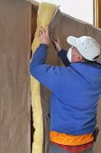 Man installing fiberglass insulation to wall cavity