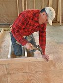 Carpenter nailing interior wall together