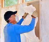 Homem instalar isolamento de fibra de vidro