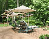 Lounge chairs under patio umbrella on deck decorated with hanging baskets of petunias