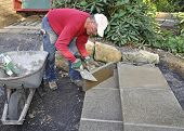 Man building patio steps using concrete pavers