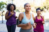 Group of curvy women jogging on track in park. Girls friends running together outdoor. Portrait of y poster