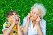 Happy Grandmother And Grandchild Fooling Around The Lawn Of Putting Chamomiles Instead Of Eyes Looki poster