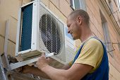 image of air conditioner  - Young setup man installs the new air conditioner for office - JPG