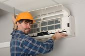 stock photo of conduction  - Repairer conducts adjustment of the indoor unit air conditioner - JPG