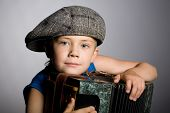 Smiling boy wearing a cap with accordion on a gray background.