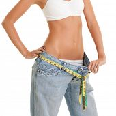 Pretty woman shows her weight loss by wearing an old jeans and measure tapes, isolated on white back