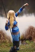 foto of fisherwomen  - beautiful blond girl fishing in pond at autumn - JPG