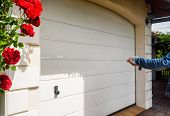 Garage Door Pvc. Hand Use Remote Controller For Closing And Opening Garage Door. poster