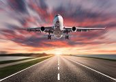 Airplane And Road With Motion Blur Effect At Sunset. Landscape With Passenger Airplane Is Flying Ove poster