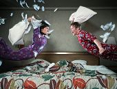 A young couple in a pillow fight
