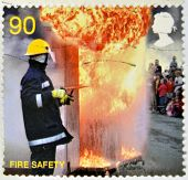UNITED KINGDOM - CIRCA 2009: a stamp printed in Great Britain shows a firefighter putting out a fire