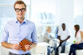 Portrait of happy man in eyeglasses holding notepad and looking at camera in working environment