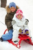Happy siblings in winterwear tobogganing in park