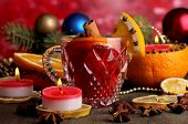 Fragrant mulled wine in glass with spices and oranges around on wooden table on red background