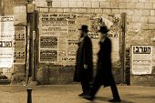 stock photo of tora  - hasidic jews walking in front of propaganda panels Jerusalem Israel - JPG