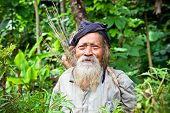 BLITAR, JAVA, INDONESIA - JANUARY 9: Old Kolufo man with bow and arrows on the natural green forest