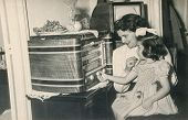 PARIS,FRANCE, CIRCA 1955 -vintage photo of mother and daughter listening to old fashioned radio, Paris, France, circa 1955