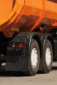 foto of chassis  - Orange dump truck chassis close to the road - JPG