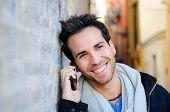 Retrato de homem bonito no fundo urbano falar ao telefone