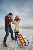 Bright picture of family couple in a winter clothes with sleigh. He warms her hands
