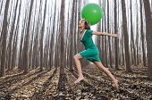 picture of vaquero  - Beautiful blonde girl dressed in green jumping into the woods with a balloon in Fuente Vaqueros Granada Spain - JPG