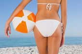 Close up of perfect young womans buttocks with beach ball on the beach