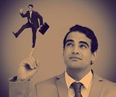 Businessman showing shrunk colleague with his briefcase posing on his finger