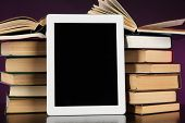 Tablet and books on bright background