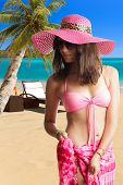 Beautiful woman with straw hat nd pink sarong on the tropical beach. Thailand.