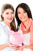 Happy women keeping savings in a piggybank - isolated over a white background