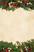 Christmas floral background border with gold baubles, holly, ivy and mistletoe on old parchment paper.