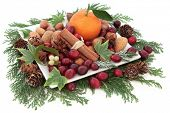 Christmas cranberry and mandarin orange fruit with nuts, spice and winter greenery over white backgr
