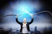 stock photo of voltage  - Image of businesswoman holding electrical cable above head - JPG
