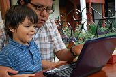 Hispanic Father Using A Computer With His Toddler Son