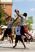 Three Men Fight For Rebound In Outdoor Street Basketball Tournament
