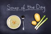 Chalkboard advertising the soup of the day, with a bowl of leek and potato soup and spoon, garnished with bread croutons, with leeks and potatoes on the side