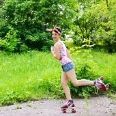 Pinup girl skating in retro roller skates in summer park, portrait of young happy sexy woman in pin-up style over nature outdoor