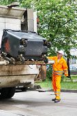 Worker of recycling garbage collector truck loading waste and trash bin