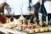 stock photo of food  - catering services background with snacks and glasses of wine on bartender counter in restaurant - JPG