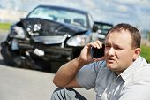 stock photo of injury  - Adult upset driver man discussing on mobile phone in front of automobile crash car collision accident in city road - JPG