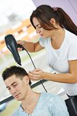 Female hairdresser drying hair with blow dryer of man client at beauty parlour