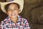 A beautiful and happy mixed race African American female girl child wearing straw cowboy hat and plaid shirt sitting in hay filled barn