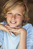 pic of freckle face  - Young happy smiling blond boy child aged about twelve or early teenager resting on his hands - JPG