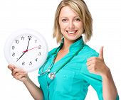 Young happy lady doctor is holding clock showing seven, isolated over white