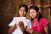 Portrait of two beautiful young traditional Myanmar girl using digital tablet pc together.