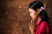 stock photo of polite girl  - Beautiful traditional Myanmar girl in a praying pose - JPG