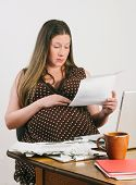 Pregnant Young Woman Reading Overdue Bills At Laptop Computer