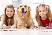 Little girls lying prone on floor, golden retriever between them.